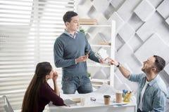 Skoncentrowany mężczyzna trzyma domową miniaturę Zdjęcia Stock