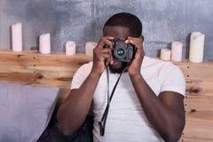 Skoncentrowany mężczyzna trzyma fotografii kamerę w łóżku fotografia royalty free