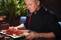 Skoncentrowany mężczyzna trzyma tacę z crayfishes obraz stock