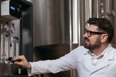 Skoncentrowany mężczyzna używa browarnianego mechanizm zdjęcia stock