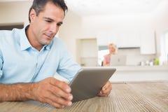 Skoncentrowany mężczyzna używa cyfrowego stół w kuchni zdjęcie royalty free