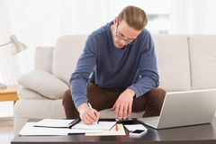 Skoncentrowany mężczyzna używa kalkulatora liczy jego rachunki obrazy royalty free