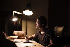 Skoncentrowany mężczyzna używa komputer dla studiować i pisać w notepad zdjęcie stock