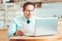 Skoncentrowany mężczyzna w fartucha działaniu zdjęcia royalty free