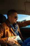 Skoncentrowany mężczyzna w okularach przeciwsłonecznych z plikiem pieniądze w ręki dri obraz stock