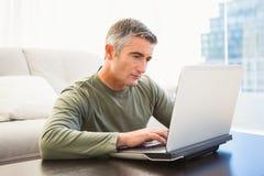 Skoncentrowany mężczyzna z popielatym włosianym używa laptopem zdjęcie royalty free