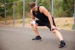 Skoncentrowany męski atlety obsiadanie na rozciąganie nogach i podłoga obraz royalty free