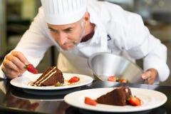 Skoncentrowany męski ciasto szef kuchni dekoruje deser zdjęcie stock