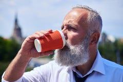 Skoncentrowany męski pijący kawową i cieszy się panoramę miasto Zdjęcie Stock
