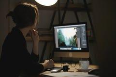 Skoncentrowany młoda dama projektant przy nocą używać komputer obrazy stock