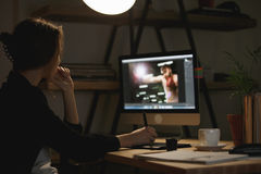 Skoncentrowany młoda dama projektant przy nocą używać komputer obraz royalty free
