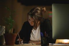 Skoncentrowany młoda dama projektanta obsiadanie w biurze zdjęcia stock
