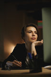 Skoncentrowany młoda dama projektanta obsiadanie w biurze przy nocą obraz royalty free