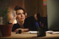 Skoncentrowany młoda kobieta projektanta obsiadanie w biurze przy nocą zdjęcie royalty free