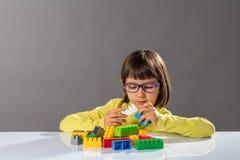 Skoncentrowany młode dziecko bawić się z elementami i kariera inżynierem obraz stock
