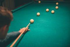 Skoncentrowany młodego człowieka bawić się Trzyma bilardową wskazówkę i celowanie łamać piłkę na łóżku stół Jest samotny w pokoju zdjęcia royalty free