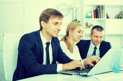 Skoncentrowany młodego człowieka kierownik pracuje na laptopie w biurze zdjęcia royalty free
