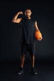 Skoncentrowany młody afrykański gracz koszykówki pokazuje bicepsy fotografia royalty free