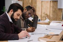 skoncentrowany młody architektów rysować architektoniczny zdjęcia stock