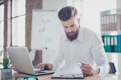 Skoncentrowany młody biznesmen pisać na maszynie informację od papierów zdjęcie royalty free