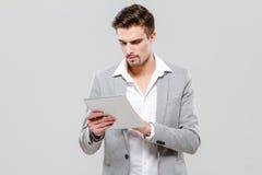 Skoncentrowany młody biznesmen używa pastylkę obrazy stock