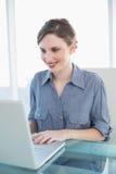 Skoncentrowany młody bizneswoman pracuje z jej notatnika obsiadaniem przy jej biurkiem zdjęcia royalty free