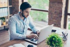 Skoncentrowany młody bliskowschodni biznesmen pisać na maszynie informat obraz stock