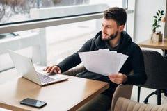 Skoncentrowany Młody Brodaty biznesmen Jest ubranym Czarnego Tshirt Pracującego laptopu Miastowej kawiarni fotografia stock