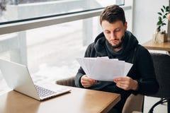 Skoncentrowany Młody Brodaty biznesmen Jest ubranym Czarnego Tshirt Pracującego laptopu Miastowej kawiarni fotografia royalty free