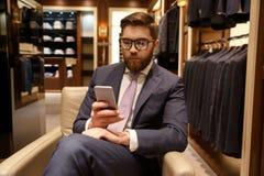 Skoncentrowany młody brodaty biznesmen siedzi indoors gawędzić obrazy royalty free