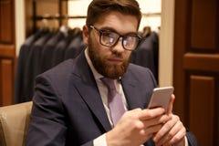 Skoncentrowany młody brodaty biznesmen siedzi indoors gawędzić zdjęcia stock