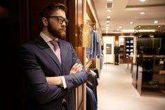 Skoncentrowany młody brodaty biznesmen stoi indoors obraz stock