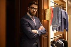 Skoncentrowany młody brodaty biznesmen stoi indoors zdjęcie stock