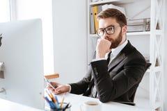 Skoncentrowany młody brodaty biznesmen używa komputer fotografia stock