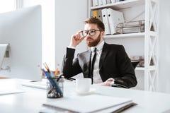Skoncentrowany młody brodaty biznesmena obsiadanie w biurze zdjęcie royalty free
