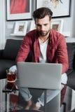 Skoncentrowany młody brodaty mężczyzna używa laptop pije herbaty zdjęcie royalty free