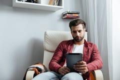 Skoncentrowany młody brodaty mężczyzna używa pastylka komputer obrazy stock