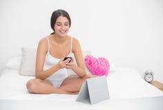 Skoncentrowany młody brown z włosami model w białych piżamach texting z telefonem komórkowym obrazy royalty free