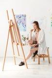 Skoncentrowany młody caucasian dama malarz przy workspace zdjęcia stock
