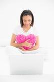 Skoncentrowany młody ciemny z włosami model cuddling poduszkę i patrzeje laptop obraz stock