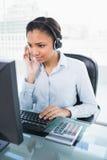 Skoncentrowany młody ciemny z włosami operator odpowiada wezwanie obraz stock