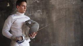 Skoncentrowany młody człowiek trzyma szermierczą maskę i rapier w po klasy ręki zdjęcie wideo