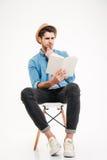 Skoncentrowany młody człowiek w kapeluszowym obsiadaniu i czytaniu książka zdjęcie royalty free