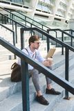 skoncentrowany młody człowiek z papierowego filiżanka kawy czytelniczą książką na schodkach zdjęcie stock