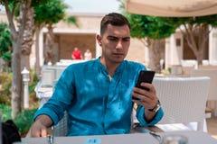 Skoncentrowany młody człowiek z smartphone na plenerowym tarasie restauracja używa smartphone obsiadanie przy stołem zdjęcia stock