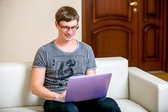 Skoncentrowany młody człowiek z szkła działaniem na laptopie w ministerstwie spraw wewnętrznych Komunikuje na ogólnospołecznych s fotografia royalty free