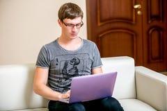 Skoncentrowany młody człowiek z szkła działaniem na laptopie w ministerstwie spraw wewnętrznych Pensively skanuje tekst na pokazi obraz stock