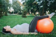 Skoncentrowany młody kobiety w ciąży lying on the beach na joga szturmanie w parkowym i patrzeje w górę Trzyma nogi balowe na pom obrazy stock