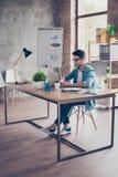 Skoncentrowany młody mądrze entrepreneuer pracuje z komputerem i obrazy stock