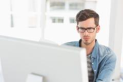 Skoncentrowany młody męski artysta używa komputer Zdjęcia Stock